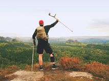 Wounded tourist with crutch above head achieved mountain peak. Hiker with  knee brace feature. Stock Images