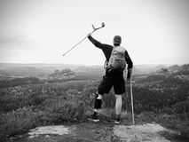 Wounded tourist with crutch above head achieved mountain peak. Hiker with  knee brace feature. Wounded tourist with crutch above head achieved mountain peak Royalty Free Stock Images