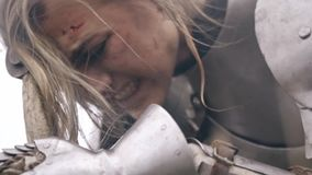 Wounded woman knight screams from grief. Jeanne D`Arc leaned against the sword and screamed in grief stock footage