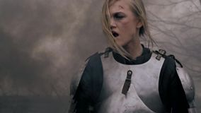 Wounded woman warrior in medieval armor wanders through the smoke. Tired Jeanne d`Arc in armor wanders in the smoke from the fire stock video footage