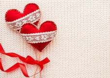 Woven background with two felt hearts with laces, symbol of love. Stock Photography
