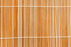 Woven Bamboo Twig Background. Background of thin, roughly hewn bamboo twigs woven together with two rougly parallel strings.  Copy space Stock Images