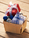 Woven basket with Chrsitmas gifts and baubles Stock Photo
