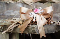 Woven basket with ribbon. On dry leaf and wooden background Royalty Free Stock Photo