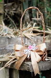 Woven basket with ribbon. On dry leaf and wooden background Royalty Free Stock Photos