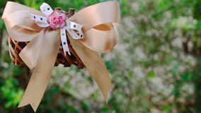 Woven basket with ribbon. On green background Stock Photos