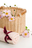 Woven basket, rolled towel and anemones Stock Photo