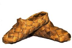 Sneaker wood woven birch sandals for everyday wear in the village on a wooden background Royalty Free Stock Photos