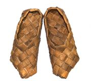 Sneaker wood woven birch sandals for everyday wear in the village on a wooden background Royalty Free Stock Image