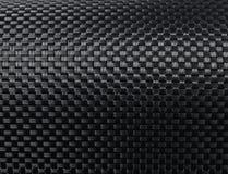 Woven carbon fibre. Black woven carbon fibre texture pattern background Royalty Free Stock Photos