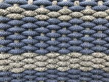 Woven grey and dark blue small tight cotton rolls as a pattern of wicker. Full frame shot of woven grey and dark blue small tight cotton rolls as a pattern of stock photos