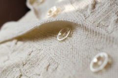Woven handicraft knit white cardigan detail. Design detail of woven handmade knit woolen design texture and button. Fabric white background stock photography