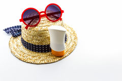Woven hat, red sunglasses with body lotion. Royalty Free Stock Images
