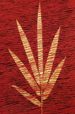 Woven leaf on red background. Yellow leaf woven into a red material background Stock Photos