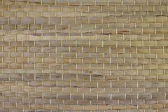 A woven Mat of reeds or straw-yellow in color. The texture of dry cane. Dark yellow. A woven Mat of reeds. The texture of dry cane. Dark yellow royalty free stock image
