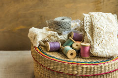 Woven rattan crafts and sewing supply box, wooden spools, rolls of lace, aged wood background, hobby clothing concept Stock Photos