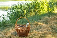 Woven vine basket, on the shores of lake on the green grass . with dishes for a picnic, in the summer clear day. Stock Image
