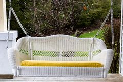 Woven white patio swing on chains. Large, white, woven patio swing on chains with yellow pillow and a garden on the background Stock Photo
