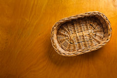 Woven wicker basket on wooden background Stock Image