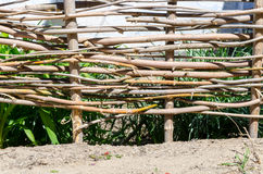 Woven wooden fence made of thin old twigs. A braided wooden fence made of thin old branches in the countryside against the backdrop of an old house royalty free stock photography