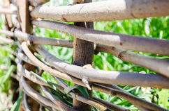 Woven wooden fence made of thin old twigs. A woven wooden fence made of thin old branches in the countryside stock photography