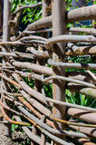 Woven wooden fence made of thin old twigs. A woven wooden fence made of thin old branches in the countryside stock photo