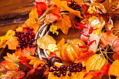 Woven wreath decorated orange leaves, autumn berries and vegetab Royalty Free Stock Photography