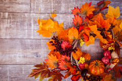 Woven wreath decorated orange leaves, autumn vegetab Stock Photos