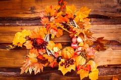 Woven wreath decorated orange leaves, autumn vegetables Stock Photos