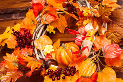 Woven wreath decorated orange leaves, autumn vegetables Royalty Free Stock Image