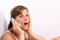 Wow - Really?. A young woman is chatting on the phone in her apartment Stock Images