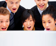 Wow, really ?!. Business group staring with mouths open in awe at a huge computer screen. Clearly surprised and astonished by something Royalty Free Stock Images
