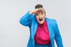 Wow! Aged woman with shocked face. Emotion and feelings, expressive grandmother with light blue suit and pink shirt standing with collected bun gray hair royalty free stock image