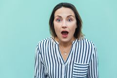 Wow! Amazed and shocked beautiful adult lady. Wow! Amazed and shocked beautiful adult lady looking at camera with shocked face. on light blue background royalty free stock photography