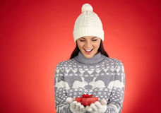Wow. Astonished girl in winterwear looking at small giftbox on her gloved palms stock photos