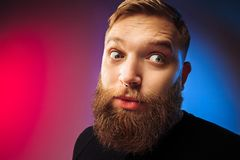The young attractive man looking suprised. Wow. Attractive male half-length front portrait on colored studio backgroud. Young emotional surprised bearded man stock photography