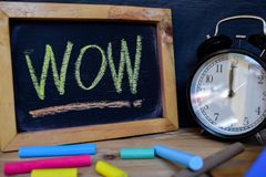 Wow. Back to school concept. Alarm clock on wooden with blackboard on background royalty free stock photography