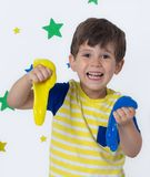Wow big slime! Children play with yellow slime. Kid squeeze and stretching goo toy stock image
