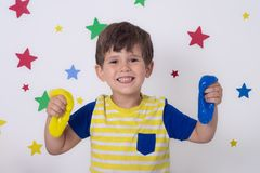 Wow big slime! Children play with yellow slime. Kid squeeze and stretching goo toy stock photography