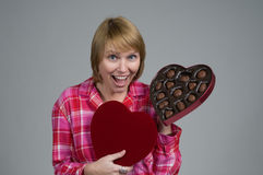 Wow chocolates for me. An attractive blonde woman receives a gift of valentines day chocolates.  Dressed in pink pattern pajamas.  Isolated on gray Royalty Free Stock Photos