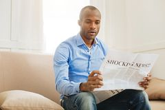 Shocked man reading a newspaper. Wow. Concentrated shocked afro-american man holding and reading a newspaper while sitting on the sofa Stock Image