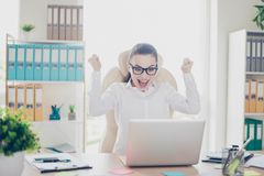 Wow! A dream of the young cute entrepreneur came true. She is very excited, wearing smart outfit, glasses, celebrating. At the work place royalty free stock images