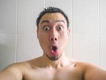 Wow e homem chocado da cara que tomam o selfie no banheiro Imagens de Stock