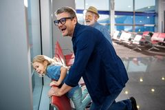 Curious relatives are waiting for flight. Wow. e view of joyful family is standing at airport lounge and looking through window with wonder. They are feeling Royalty Free Stock Photography