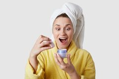 Wow, est-il pour moi ? L'heureuse femme européenne comblée regarde heureusement, tient la crème, porte la serviette et le peignoi photographie stock libre de droits