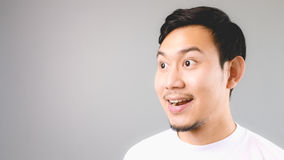 Wow face on empty copyspace. An asian man with white t-shirt and grey background stock photos