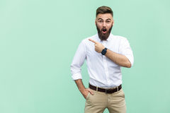 Wow! Handsome young adult man with beard in shoked. Pointing away while standing isolated on light green background stock photos