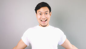 Wow, he is happy and ready to hug you. An asian man with white t-shirt and grey background royalty free stock photography
