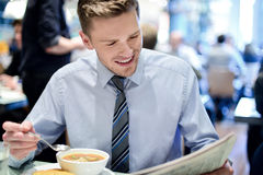 Wow, its a really great news. Happy executive reading a journal in cafe stock image