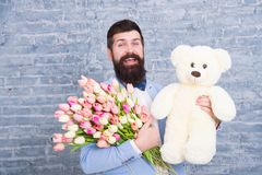 Wow. Love date. international holiday. Spring gift. Bearded man hipster with flowers. Bearded man with tulip bouquet and royalty free stock photos